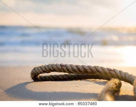 Old rope on the beach at sunrise