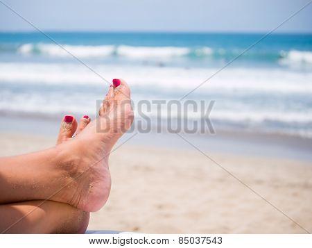 woman's sandy feet on the beach