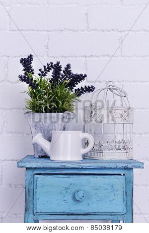 Interior design with plant, decorative cage and watering pot on tabletop on white brick wall background