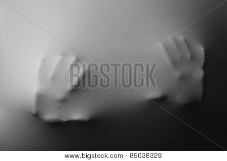 Human hands pressing through fabric as horror background