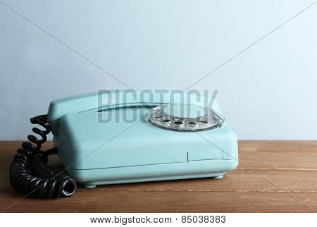 Retro telephone set on wooden table and light colorful background