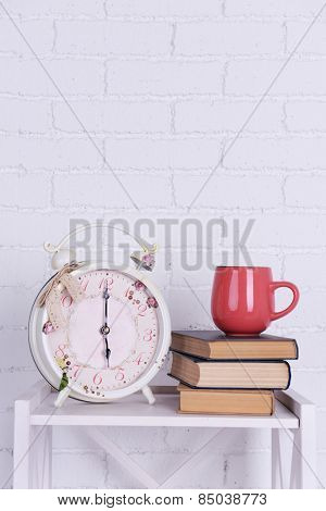 Interior design with alarm clock, stack of books and pink cup on tabletop on white brick wall background