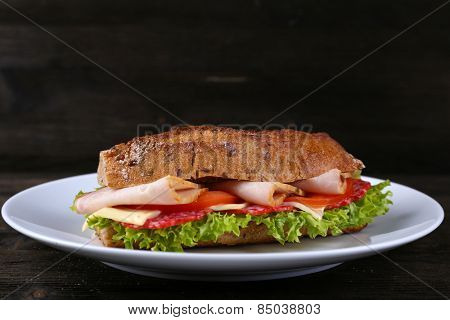 Fresh and tasty sandwich with cheese and vegetables on plate on wooden background