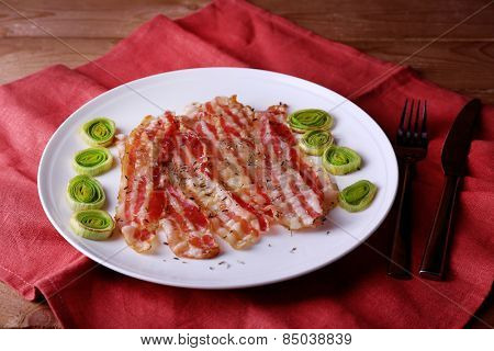 Strips of bacon with slices shallot in white plate with napkin on wooden table background