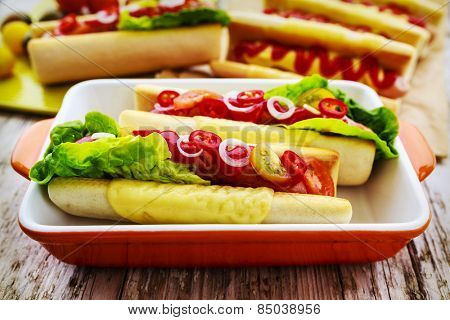 Grilled hot dogs with ketchup, mustard and relish on a table background.