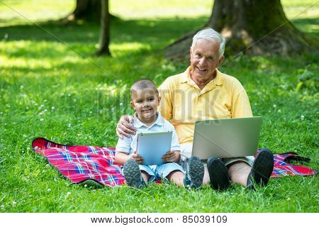grandfather and child using tablet computer in park