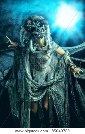 Frightening female wearing mask of skull. Fantasy. Halloween. Witchcraft, voodoo dances.