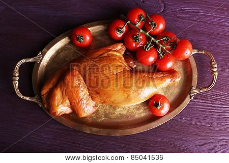Smoked chicken leg with cherry tomatoes on metal tray on color wooden table background