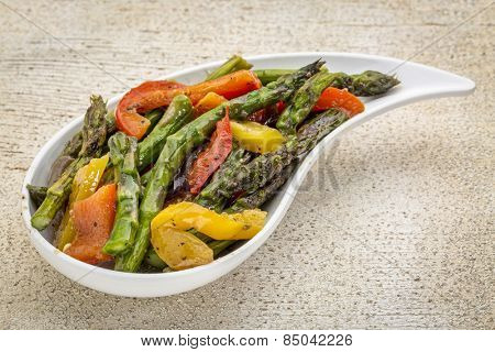 roasted asparagus salad with bell pepper on a teardrop shaped bowl against white painted rustic wood