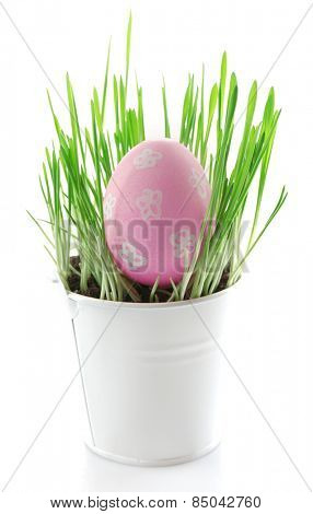 Fresh green grass in small metal bucket and Easter egg, isolated on white