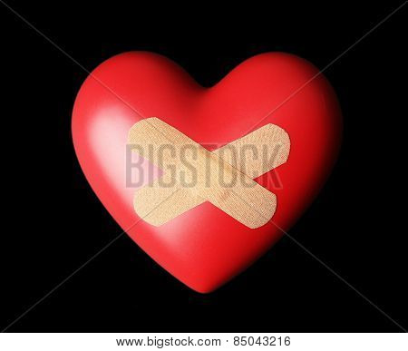 Heart with plaster on black background
