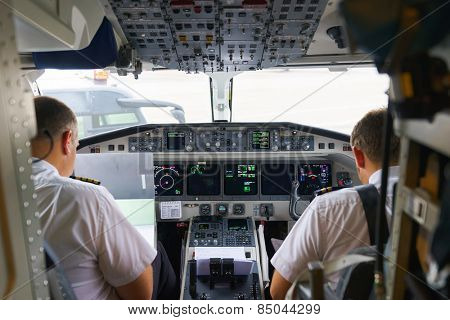 GENEVA - SEPTEMBER 11: Etihad Regional pilots in aircraft cockpit on September 11, 2014 in Geneva, Switzerland. Darwin Airline, operating under the brand name Etihad Regional since January 2014