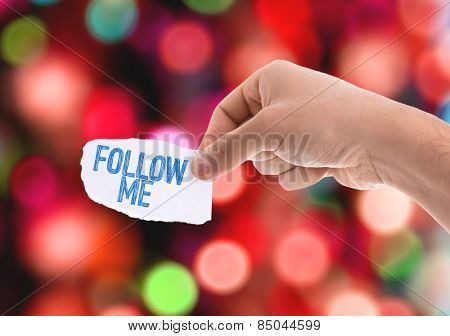 Follow Me piece of paper with bokeh background