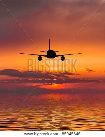 The plane flies over the sea at sunset