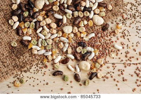 Assorted garden seeds scattered over burlap on rustic wood background.  Seeds include various beans, peas, corn, radishes, and carrots.