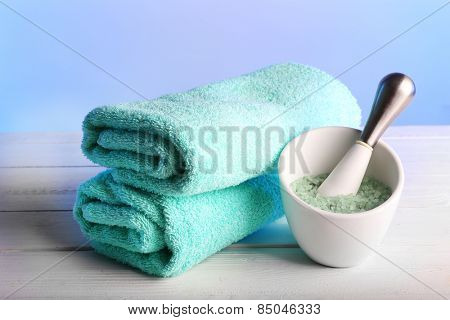 Terry towels with cup of sea salt on wooden table and light colorful background