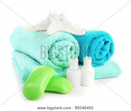Towels with shampoo bottles, starfish and soap isolated on white