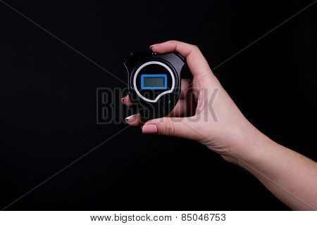 Electronic sport timer in  female hand on black background