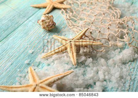 Sea stars on sea salt on wooden background