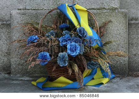 Blue flowers in a basket decorated with Ukrainian national flags.