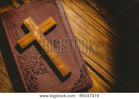Crucifix icon on the bible on wooden table