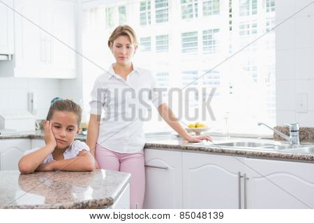 Mother and daughter after an argument at home in kitchen