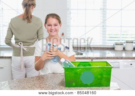 Happy little girl holding recycling bottles at home in the kitchen