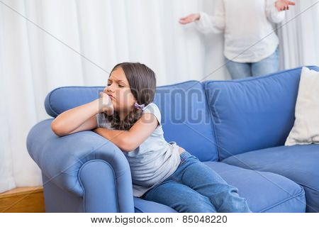 Angry little girl sitting on the couch in the living room