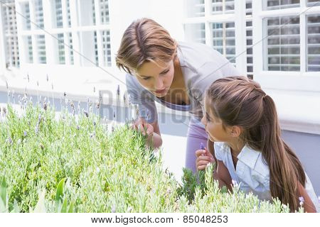 Mother and daughter tending to flowers outside in the garden