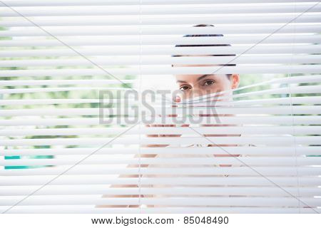Woman peeking through blinds from outside