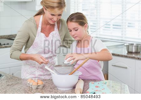 Mother and daughter making cake together at home in the kitchen