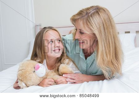 Happy mother and daughter smiling at each other in bed