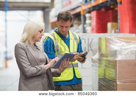 Manager using tablet while worker scanning package in warehouse