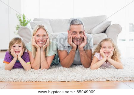 Portrait of parents and children with head in hands lying on rug at home