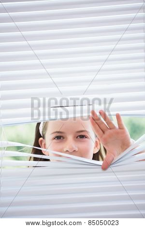 Little girl peeking through blinds from outside