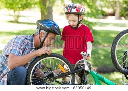 Father and son fixing a bike on a sunny day