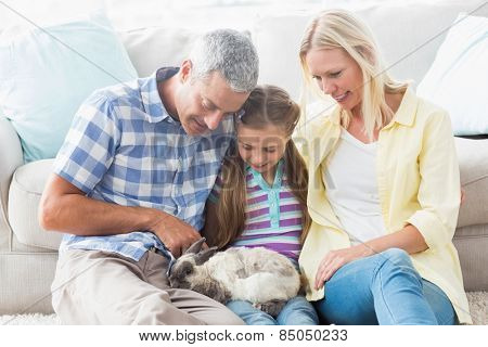 Happy parents and daughter playing with rabbit at home in living room