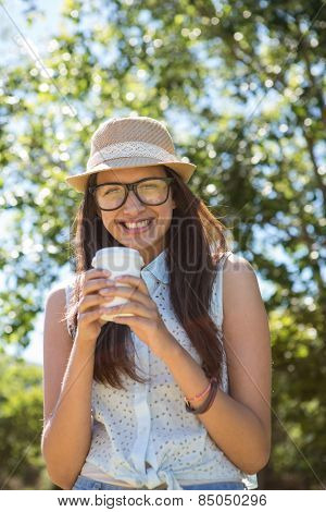 Pretty brunette having coffee to go on a summers day