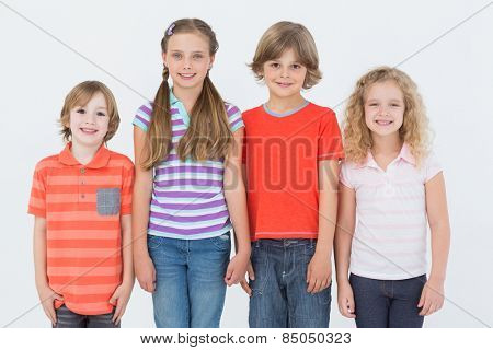 Portrait of happy children standing side by side on white background