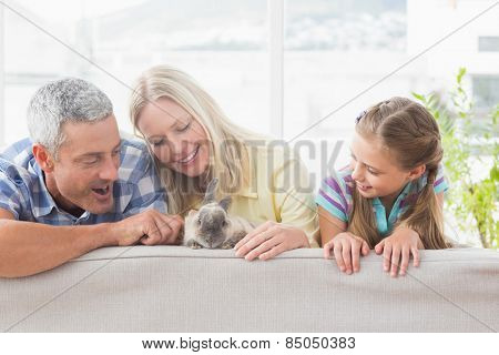 Happy family playing with rabbit on sofa at home
