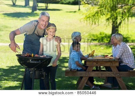 Happy father doing barbecue with his daughter on a sunny day
