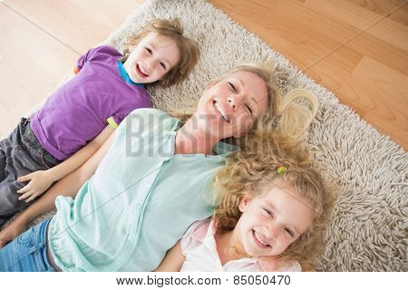 High angle view of happy mother and children lying on rug at home