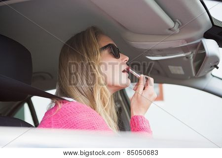 Young woman putting on makeup in her car