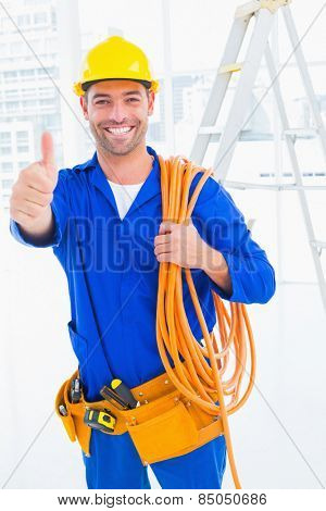 Portrait of male technician with wire roll gesturing thumbs up in bright office