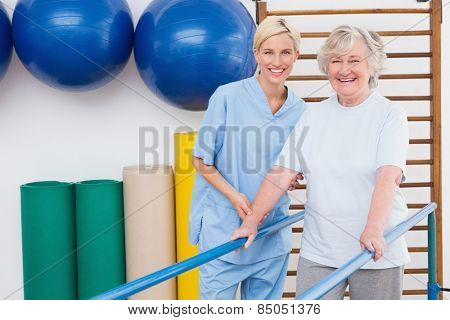 Senior woman and therapist smiling at camera in fitness studio