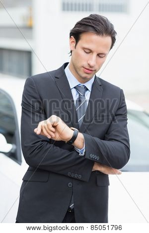 Businessman checking time outside his car