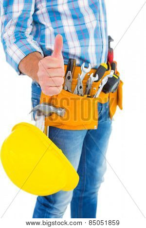 Midsection of manual worker gesturing thumbs up on white background