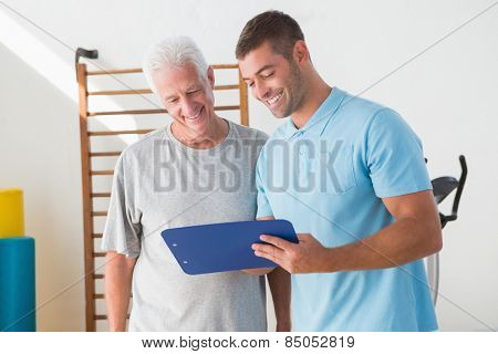 Senior man with coach looking at clipboard in fitness studio