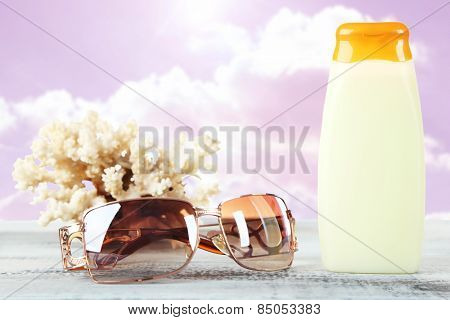 Bottle of suntan cream with sunglasses and coral on table isolated on white