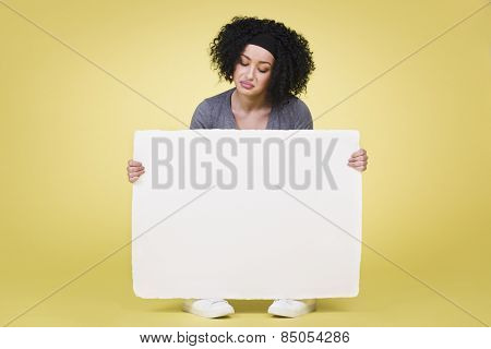 Displeased unhappy girl holding a white paper sign board with empty copy space, isolated on yellow background.
